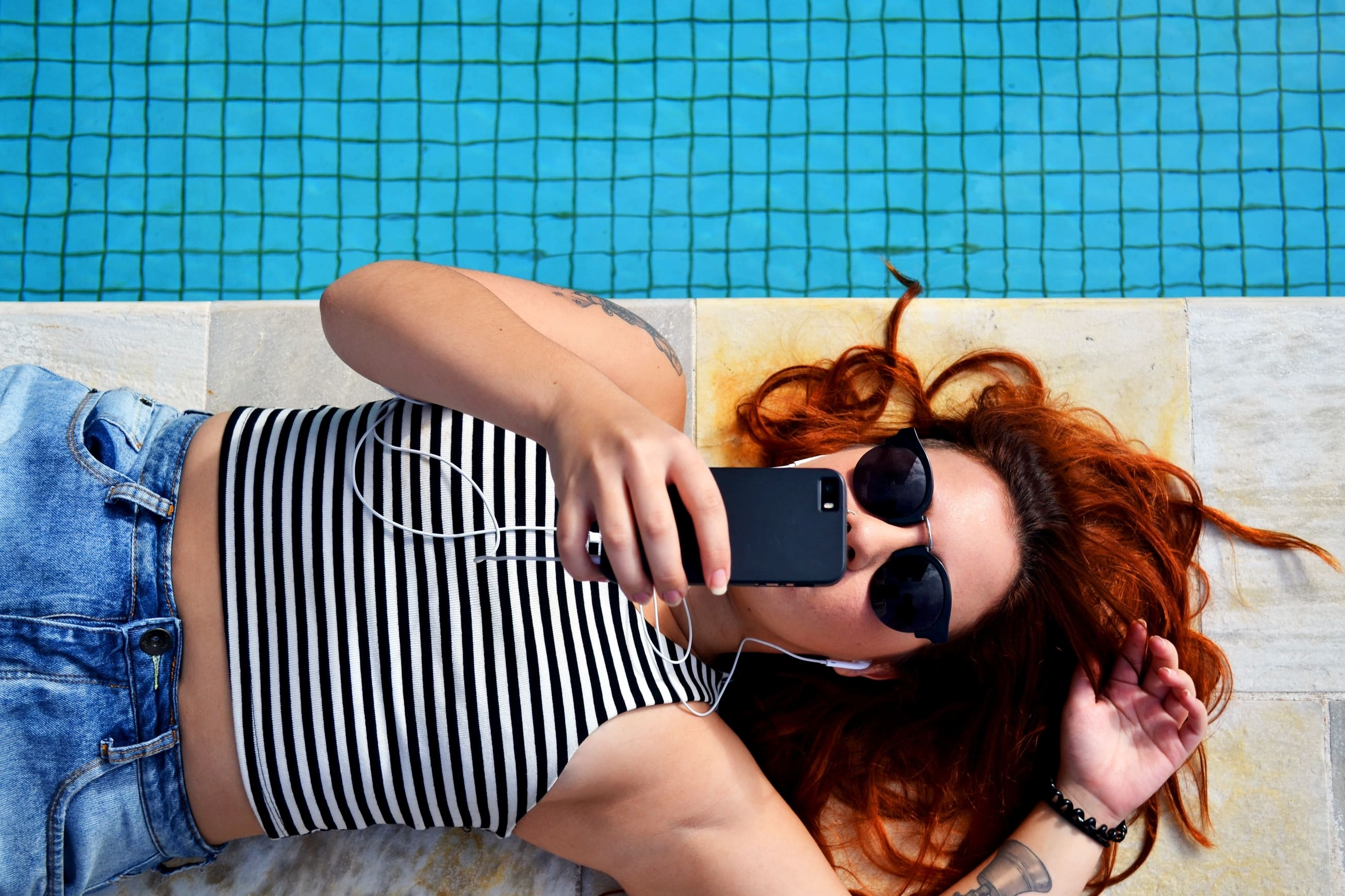 woman listening to music by pool