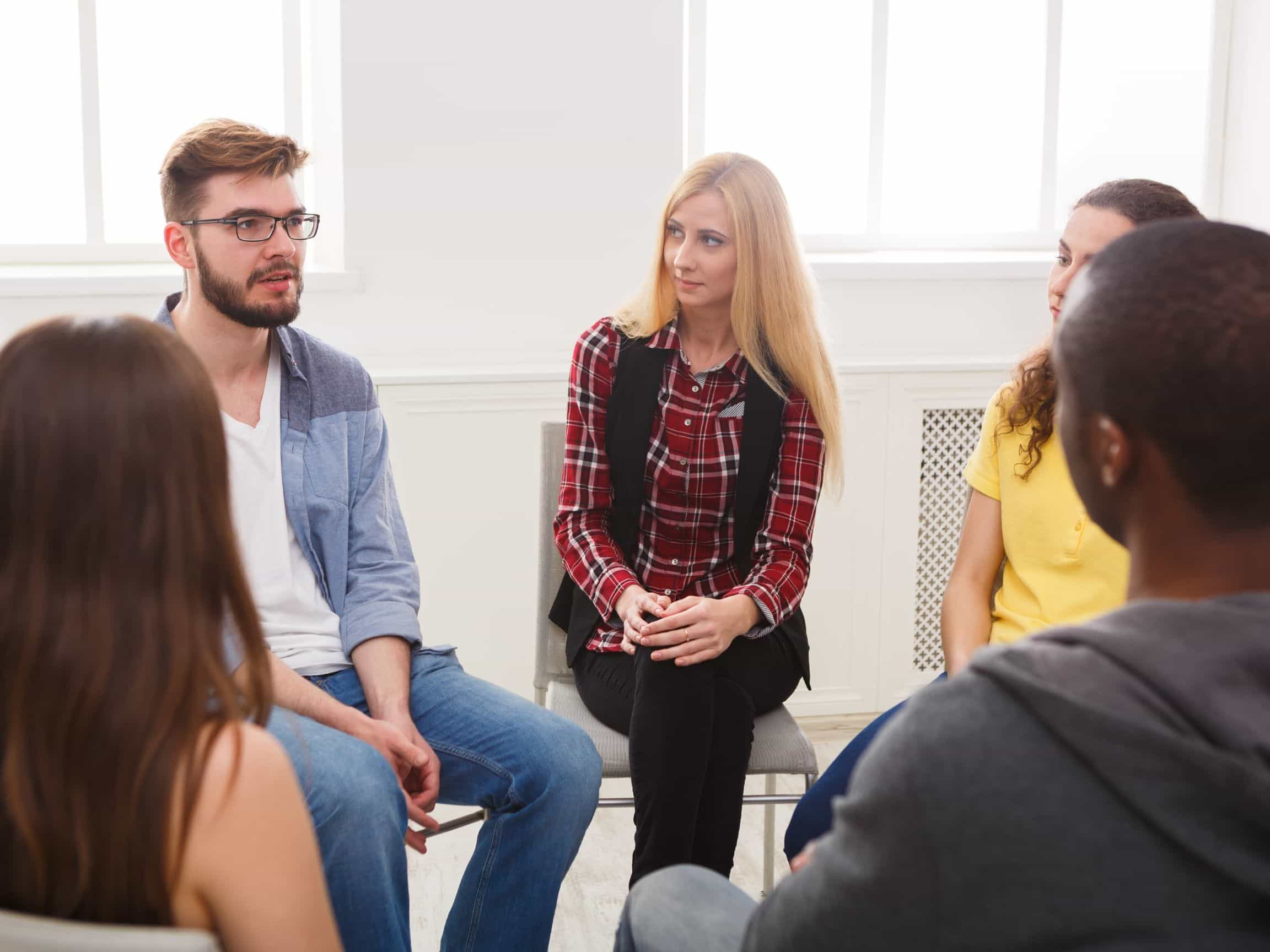 People sit in a circle during a group therapy session