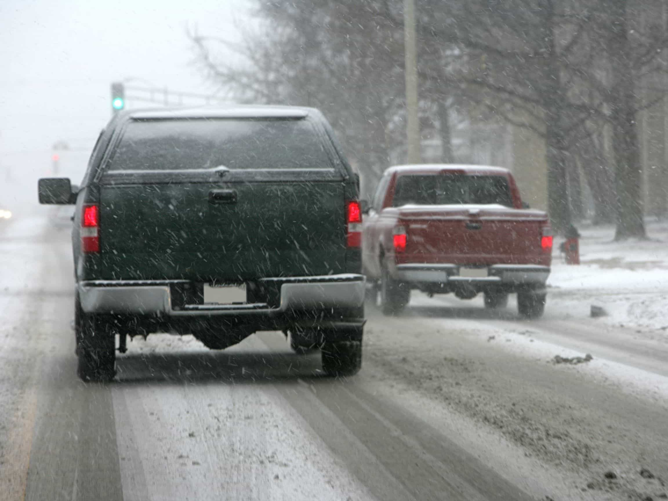 Two trucks driving on a snowy road