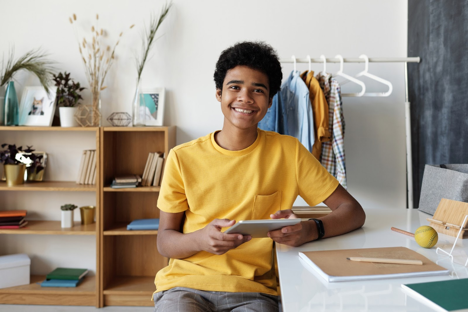 Cheerful teen smiling at the camera with his tablet in his hand